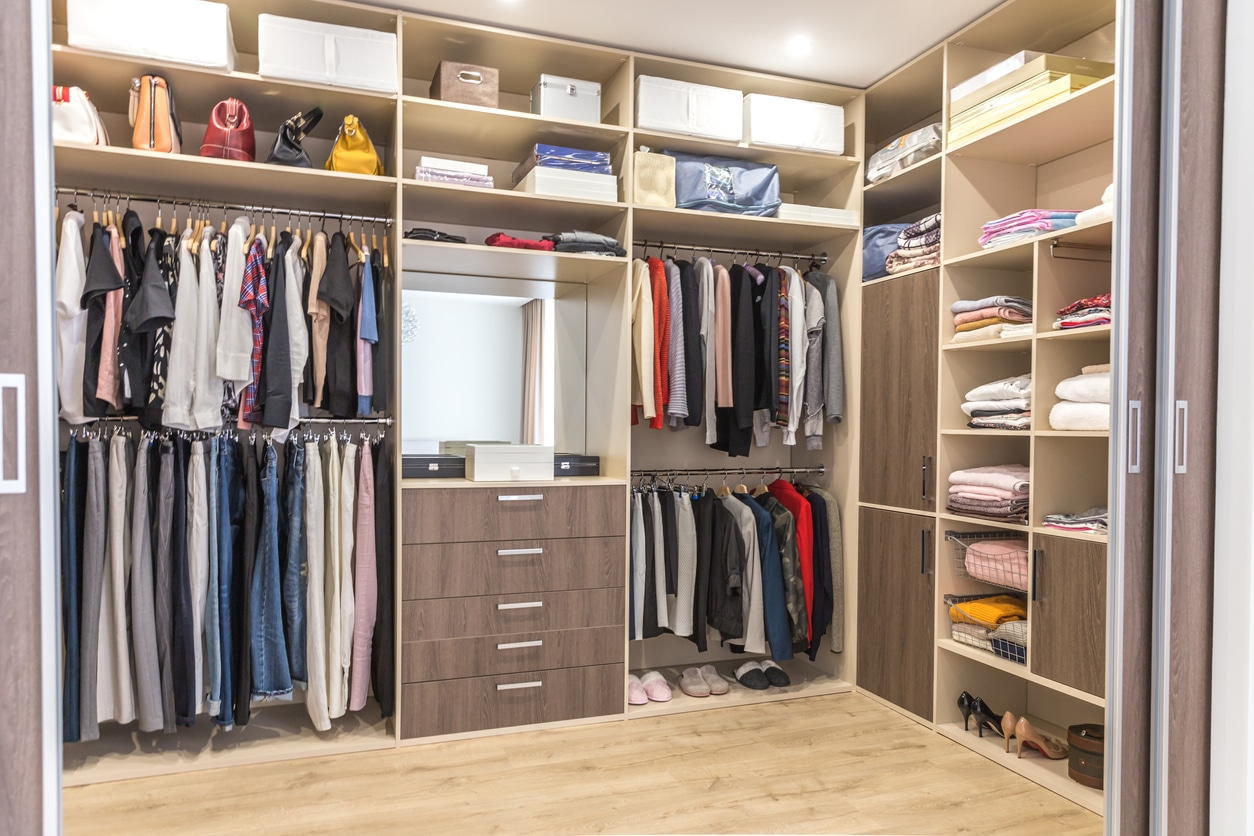 Big wardrobe with different clothes for dressing room. Walk in closet