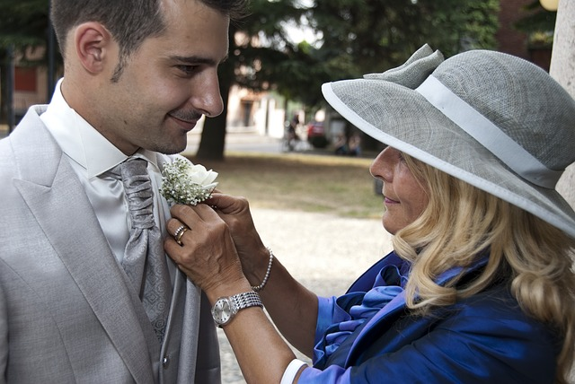 Mother of the Groom adding buttonhole to groom's outfit
