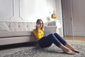 Woman on phone and laptop in her lounge